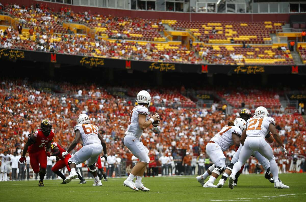 Texas quarterback Sam Ehlinger, center, looks for a receiver in the first half of an NCAA college football game against Maryland, Saturday, Sept. 1, 2018, in Landover, Md. (AP Photo/Patrick Semansky)