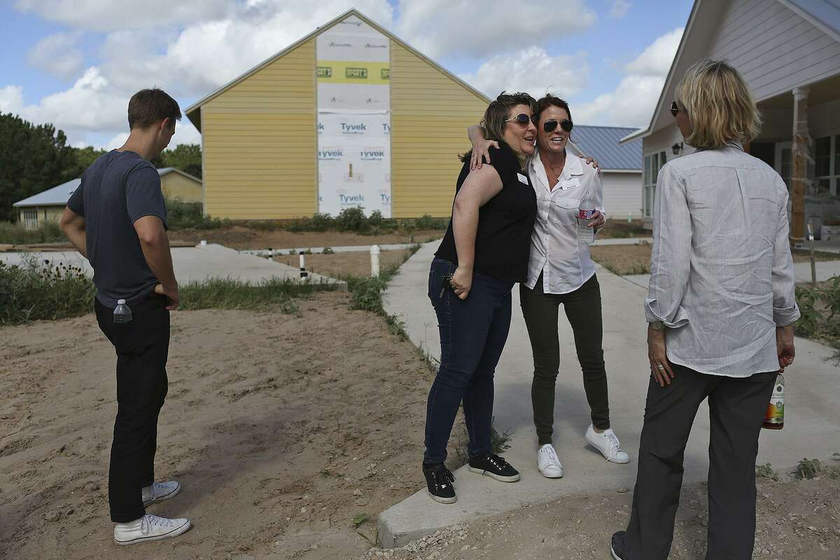 Toni McKinley (left), director of survivor services for the Refuge, embraces Monica Hinkle, director of community engagement, as they gather with others for a tour of the facility near Bastrop in June.