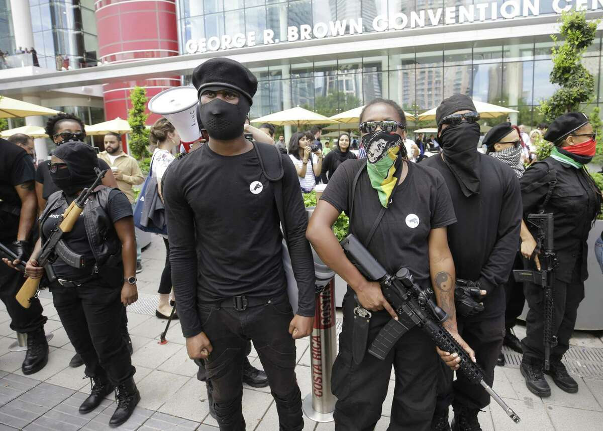 Members of the Black Panthers carry weapons as they counterprotest against other protesters outside the Islamic Society of North America Convention at the George R. Brown Convention Center, 1001 Avenida de las Americas, Saturday, Sept. 1, 2018, in Houston.