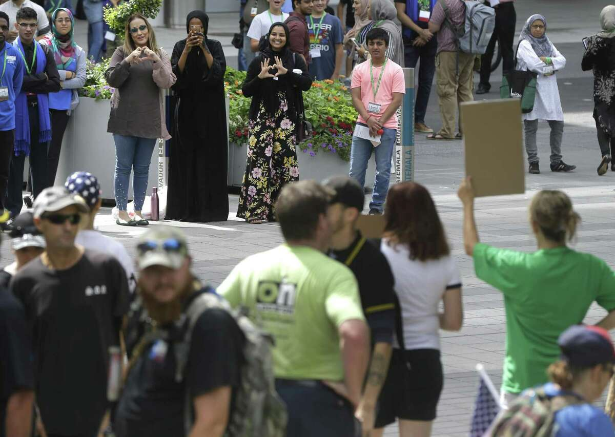 Women attending the Islamic Society of North America convention make heart signs toward the Texas Patriot Network and other groups protesting outside the George R. Brown Convention Center on Saturday.