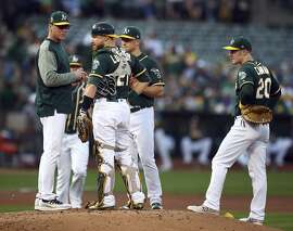 Oakland Athletics manager Bob Melvin, left, speaks to catcher Jonathan Lucroy as they wait for a new pitcher during the second inning of a baseball game against the Seattle Mariners on Saturday, Sept. 1, 2018, in Oakland, Calif. (AP Photo/Ben Margot)