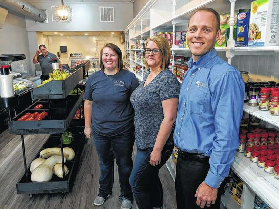 Great Scott Community Market employee Mazi Walker (from front left), manager Sarah Lashmett and Bryan Hubbert, treasurer for the market's board of directors, stand at the front of the market.
