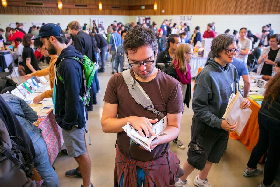 Gavin Morgan dives into reading a zine at the S.F. festival for self-published authors in Golden Gate Park. Photo: Peter DaSilva / Special To The Chronicle