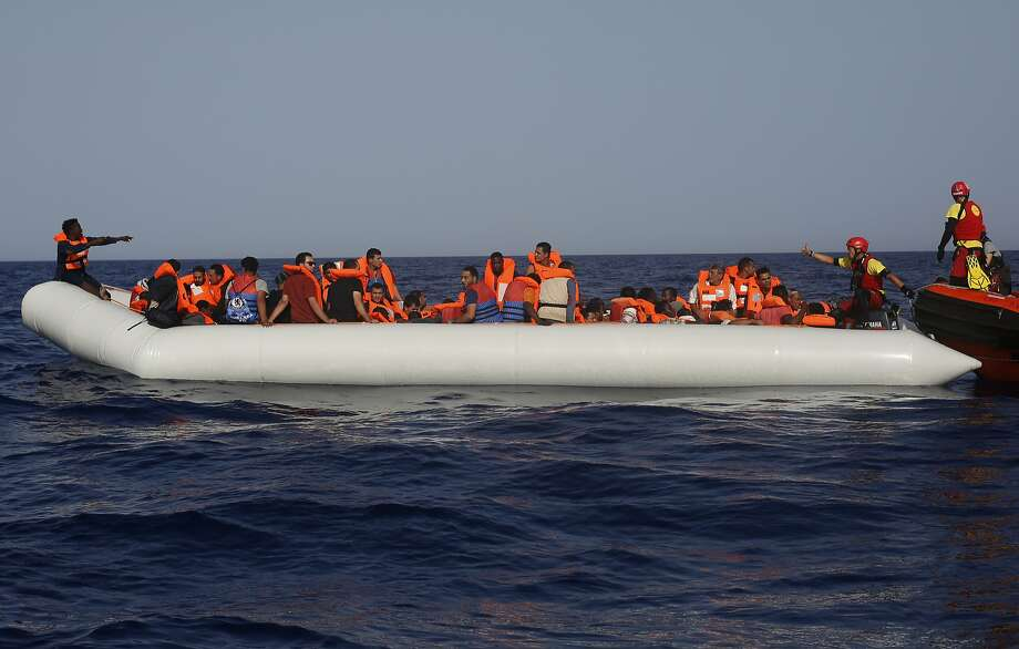 An Open Arms lifeguard gives a thumbs-up to a migrant at the other end of a rubber boat in the middle of a rescue operation off the coast of Libya in the Mediterranean Sea. Photo: Renata Brito / Associated Press