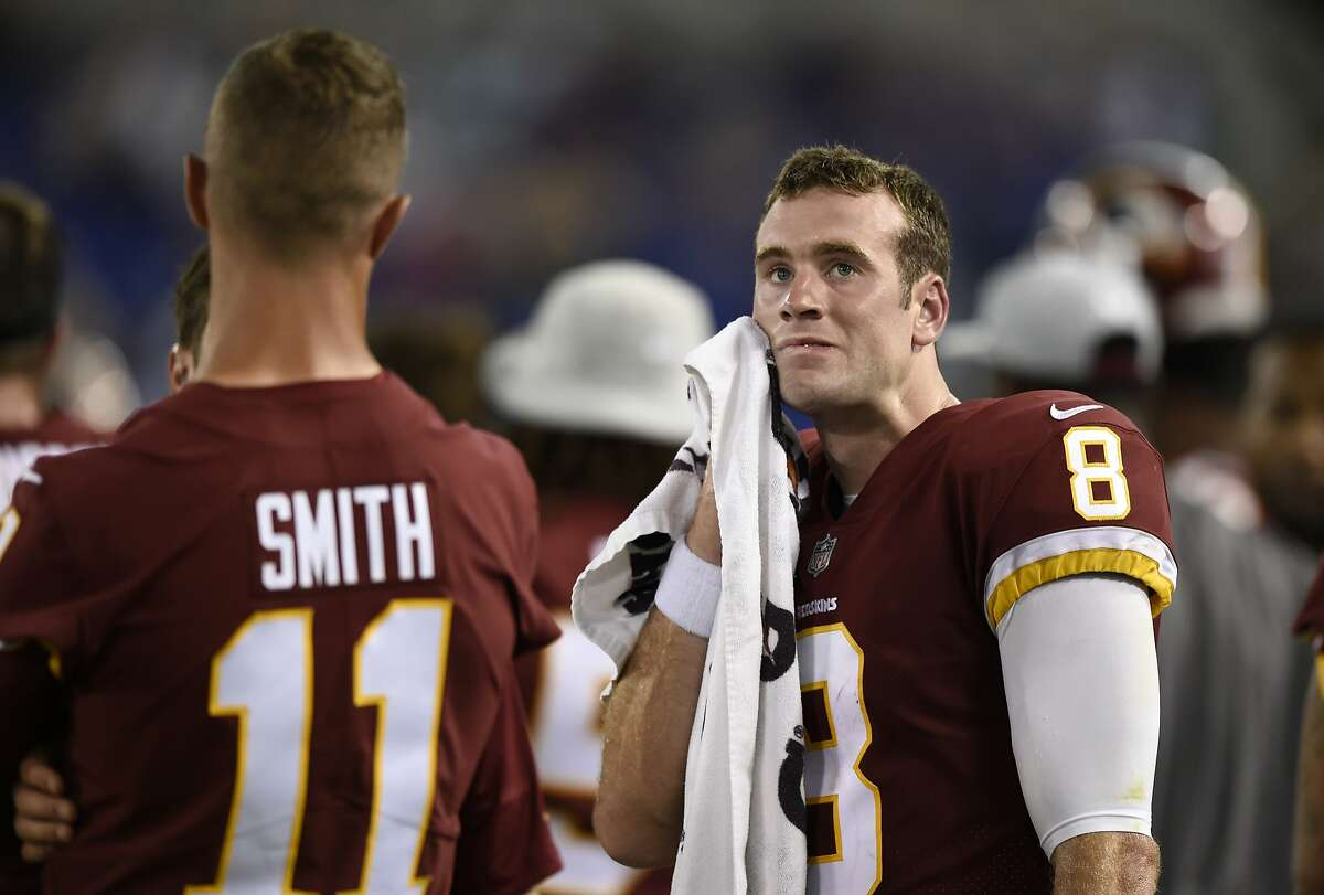 Washington Redskins quarterback Kevin Hogan, right, wipes his face as he stands on the sideline with quarterback Alex Smith (11) in the second half of a preseason NFL football game against the Baltimore Ravens, Thursday, Aug. 30, 2018, in Baltimore. (AP Photo/Gail Burton)