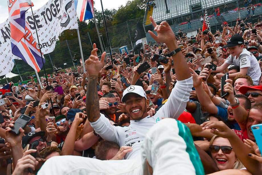 Formula One points leader Lewis Hamilton gets carried away by the crowd afte winning the Italian Grand Prix in Monza. Photo: MIGUEL MEDINA;Miguel Medina / AFP / Getty Images