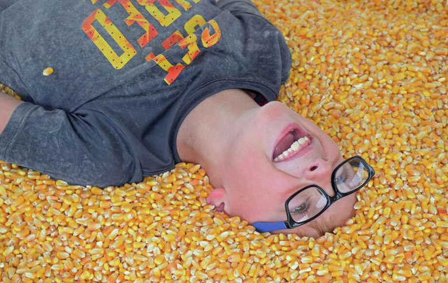 Seven-year-old Tanner Mills, of Godfrey, plays in the Glazebrook Park corn crib during the Great Godfrey Maze this weekend. Photo: David Blanchette | For The Telegraph