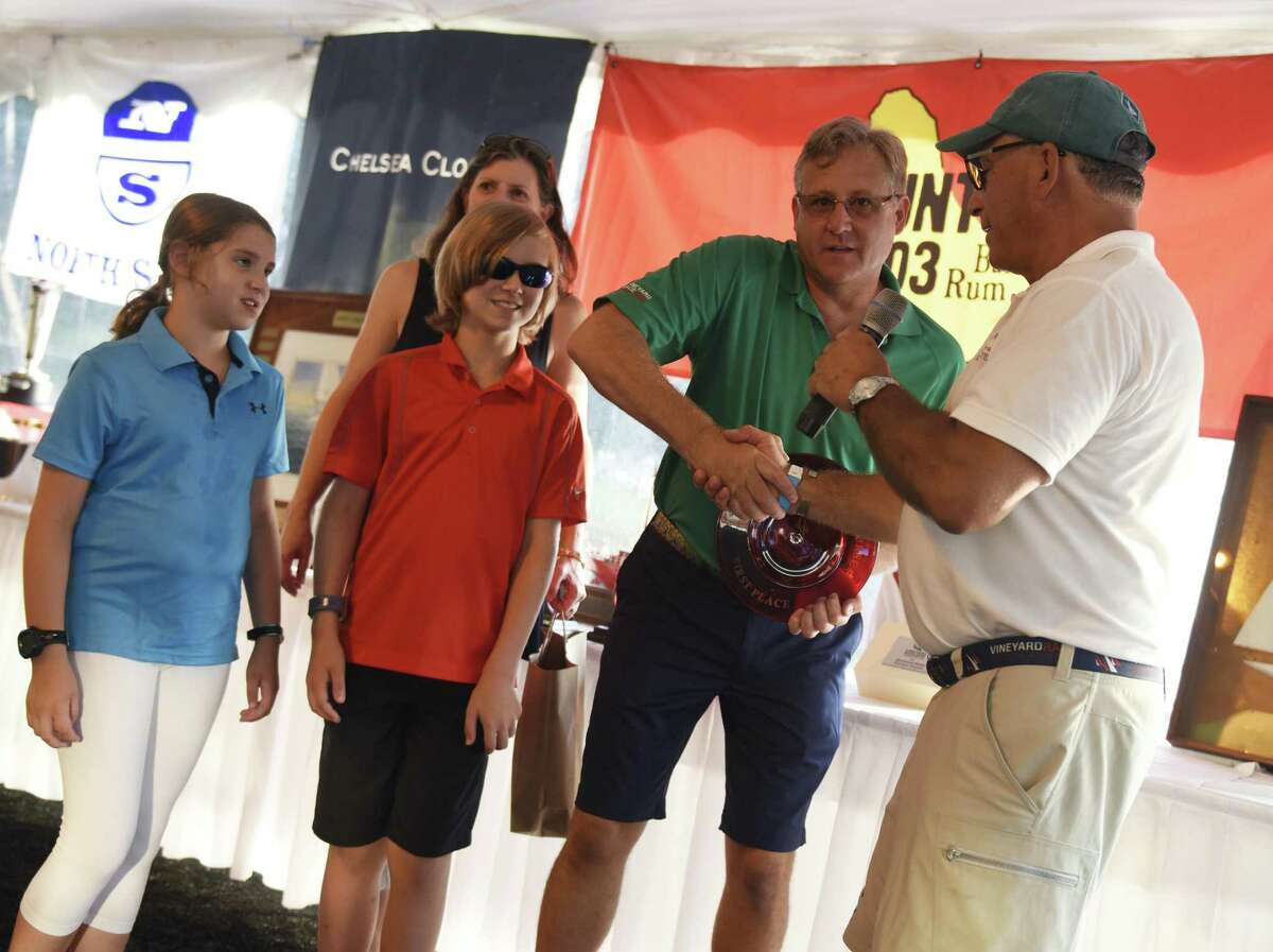 Wilton's Austin Royle accepts his first place PHRF Class III award with his wife, Kathleen, and children, Alison, 10, and Cameron, 12, at the Vineyard Race trophy presentation ceremony at the Stamford Yacht Club in Stamford on Sunday.
