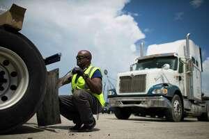 Adam Garrett, 59, installs mud flaps to his truck at the Port Auto Truck Stop, Monday, Aug. 27, 2018, in La Porte. Garrett is a local trucker.