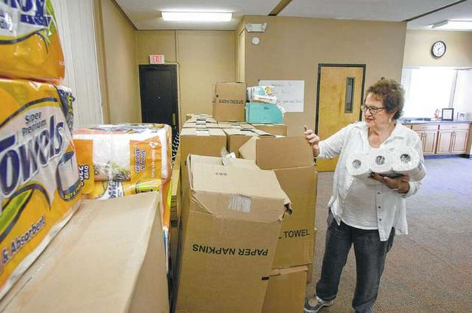 Karen Daudelin, Wesley United Methodist Church paper distribution lead, looks through a recent delivery of paper products from Midwest Food Bank in the basement of a former bank building in Bloomington. The church has opened Wesley West, where the focus on paper items came from the fact that people using Link cards cannot purchase paper products when they shop for groceries. Photo: David Proeber | The Pantagraph (AP)