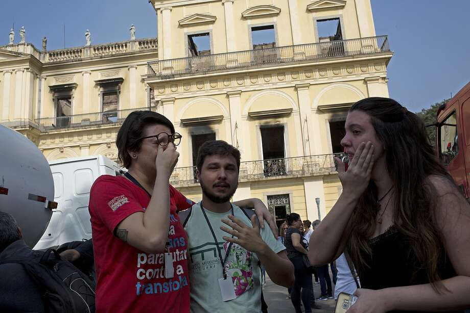 National Museum employees console each other outside the burned structure in Rio de Janeiro. The museum held Latin America's largest archive of artifacts, objects and documents. Photo: Silvia Izquierdo / Associated Press