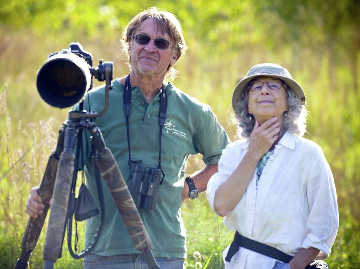 From left, Dave Winston of Stamford, Head Stewart of the Cove Island Wildlife Sanctuary and visitor Joan Ross of Stamford watch and photograph various migrating birds and butterfly's inhabit the summer sanctuary on Sept. 1, 2018 in Stamford, Connecticut.
