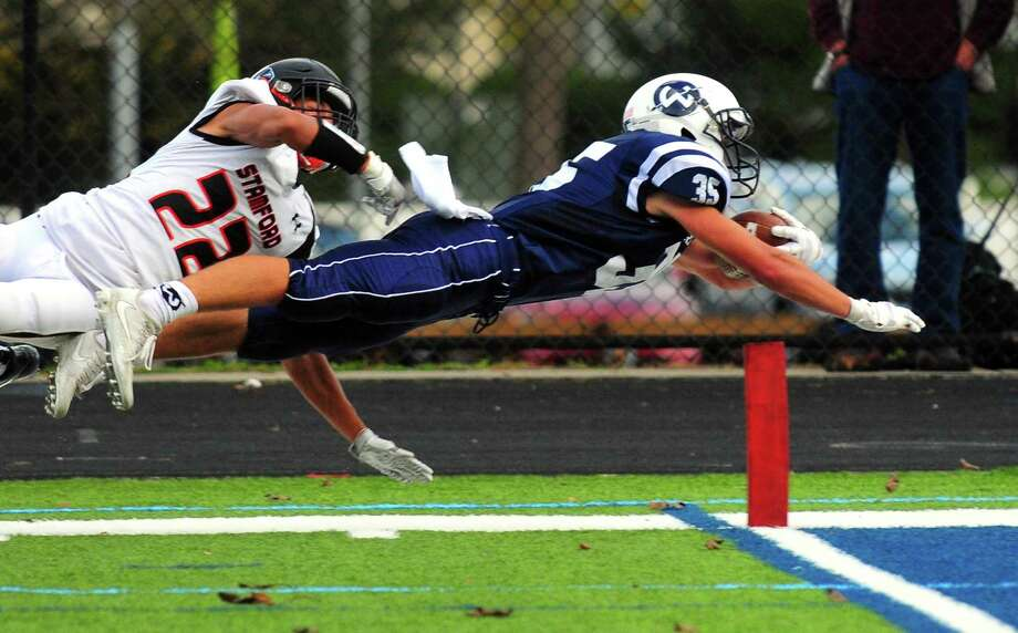 Wilton's Drew Herlyn 	dives in an attempt to reach the end zone during football action against Stamford in Wilton, Conn. on Saturday Oct. 28, 2017. Herlyn fell short in the attempt. At left is Stamford's Julius Page. Photo: Christian Abraham / Hearst Connecticut Media / Connecticut Post