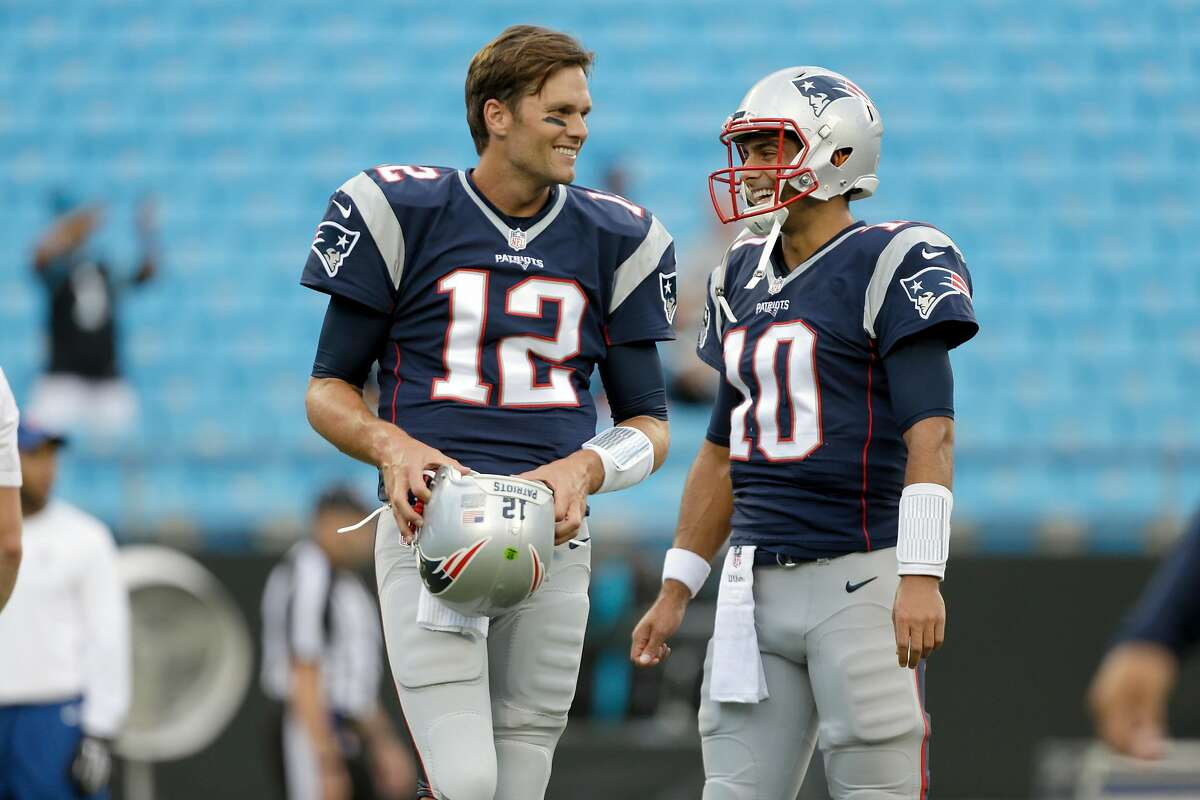 Then-Patriots quarterbacks Tom Brady and Jimmy Garoppolo laugh before a 2016 game against the Carolina Panthers in Charlotte, N.C. Now Brady is a Buccaneer and Garoppolo a 49er.