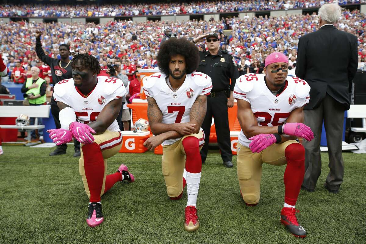 Eli Harold #58, Colin Kaepernick #7 and Eric Reid #35 of the San Francisco 49ers kneel in protest on the sideline, during the anthem, prior to the game against the Buffalo Bills at New Era Field on October 16, 2016 in Orchard Park, New York.Kaepernick has a new deal with Nike, even though the NFL does not want him.