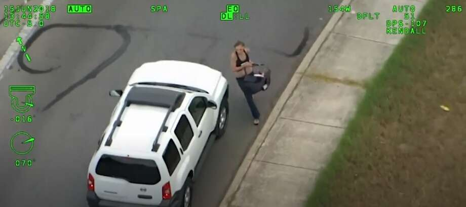 Authorities released video showing a woman driving an SUV speeding away from police stop, swerving in and out of traffic until she crashes. Then pulling a baby out of vehicle and runs off. (Sept. 3) Photo: Associated Press