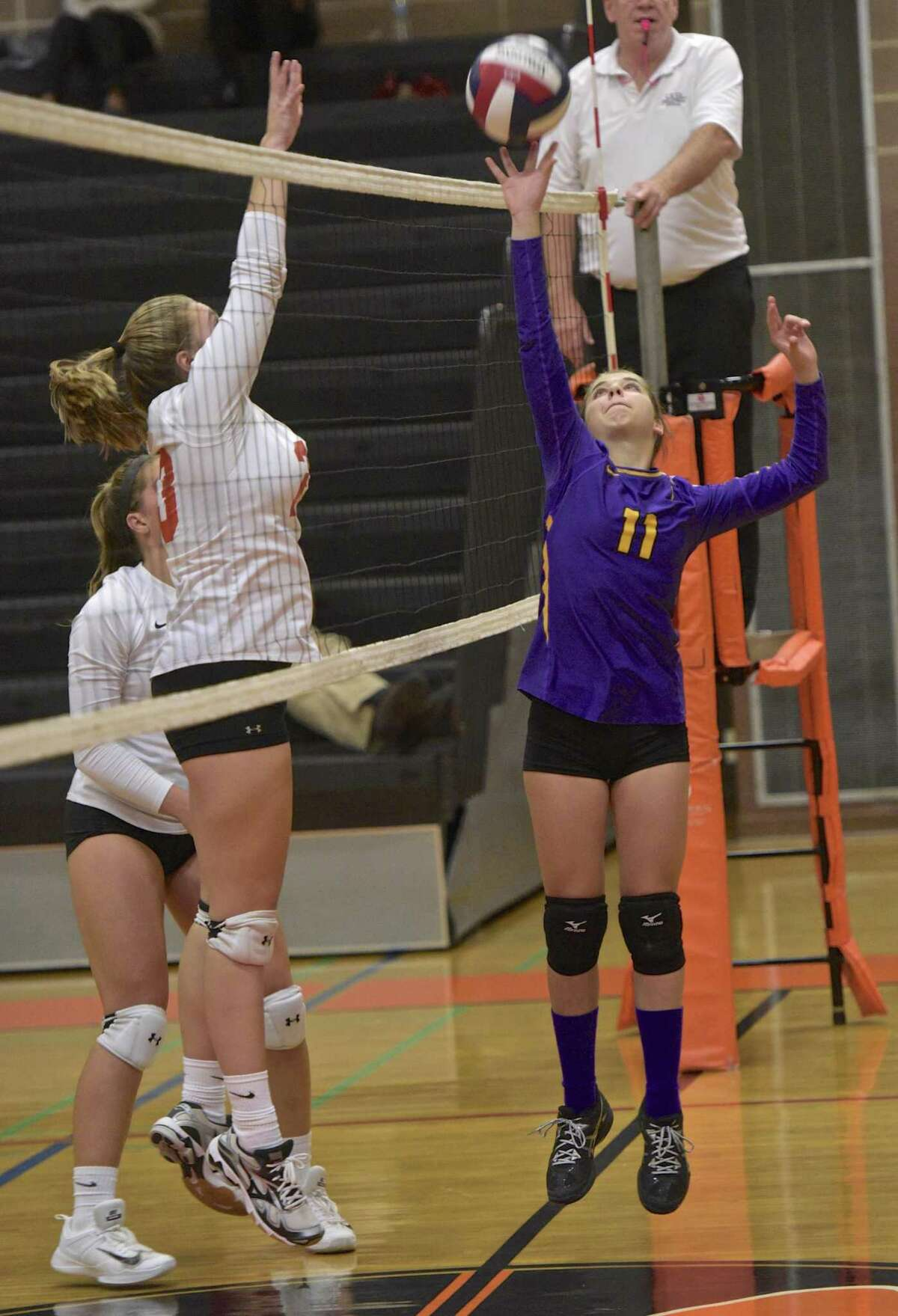 Westhill's Vanna Servos (11) taps the ball over the net as Ridgefield's Olivia Lescinskas (23) goes up for the block in the girls volleyball game between Westhill and Ridgefield high schools on Oct. 25, 2017, at Ridgefield High School, in Ridgefield, Conn.