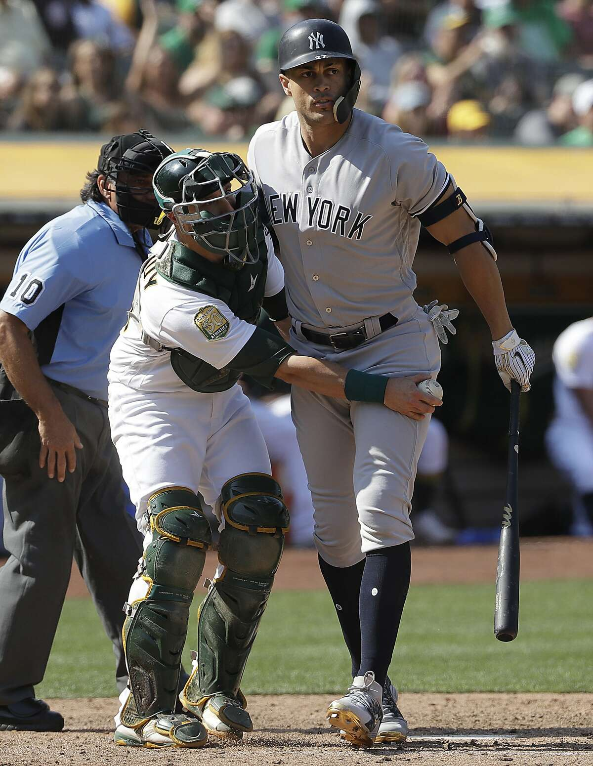 Oakland Athletics catcher Jonathan Lucroy, center, tags New York Yankees' Giancarlo Stanton after Stanton struck out during the eighth inning of a baseball game in Oakland, Calif., Monday, Sept. 3, 2018. (AP Photo/Jeff Chiu)