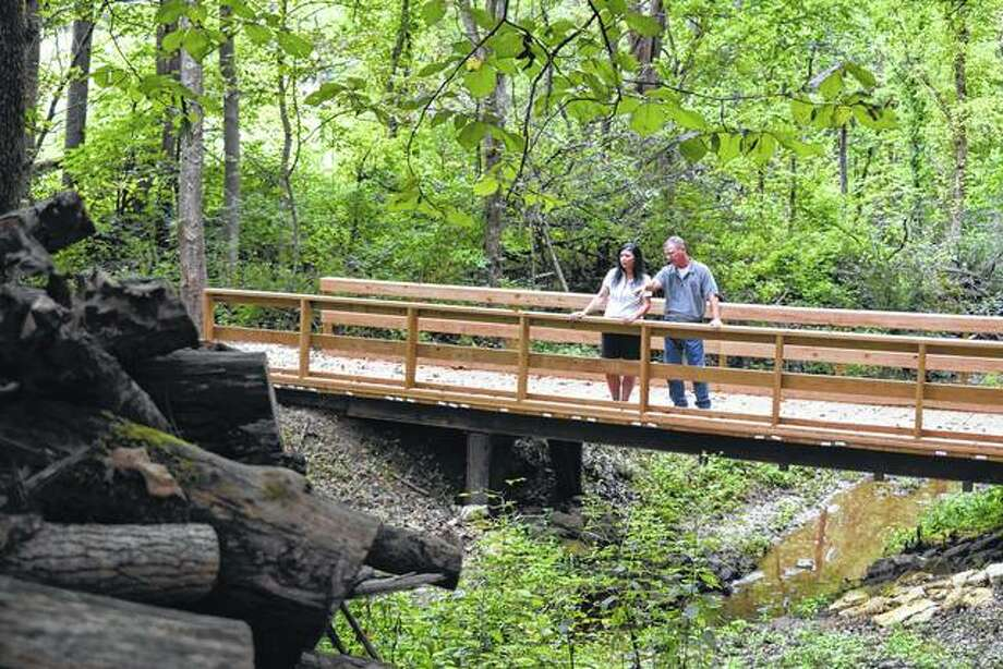 Laura and Drew Dukett, owners and operators of Doe Run Education Works, a nature center northwest of Roodhouse, stand on a bridge in the nature center. Photo: Greg Olson | Journal-Courier