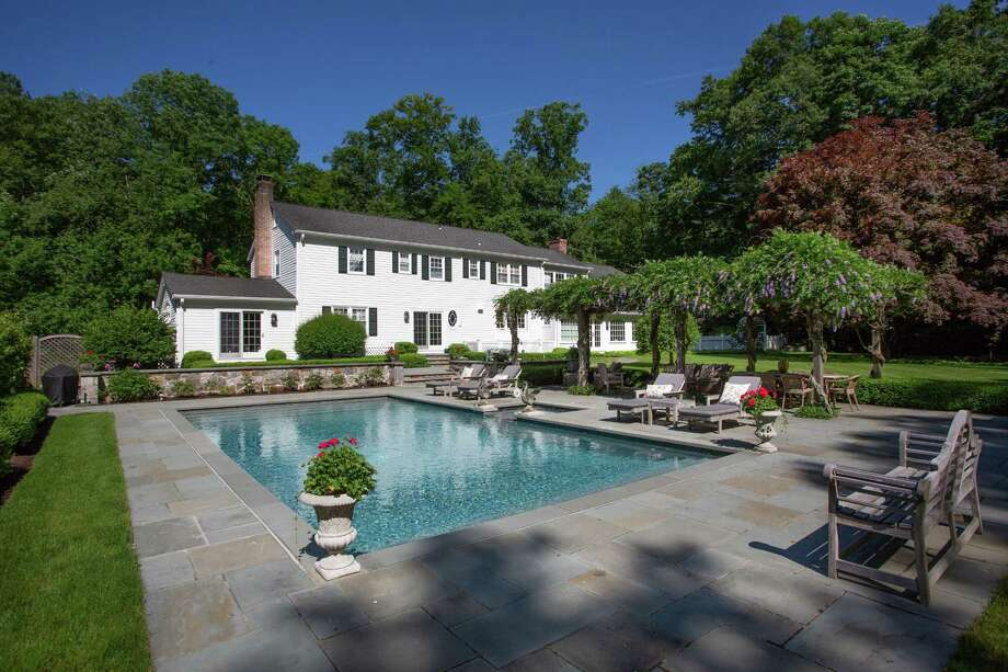 The 11-room colonial house at 235 Laurel Road sits on an attractively landscaped two-acre level property with a heated in-ground swimming pool, spa, slate terrace, wisteria-covered pergola, and specimen plantings.