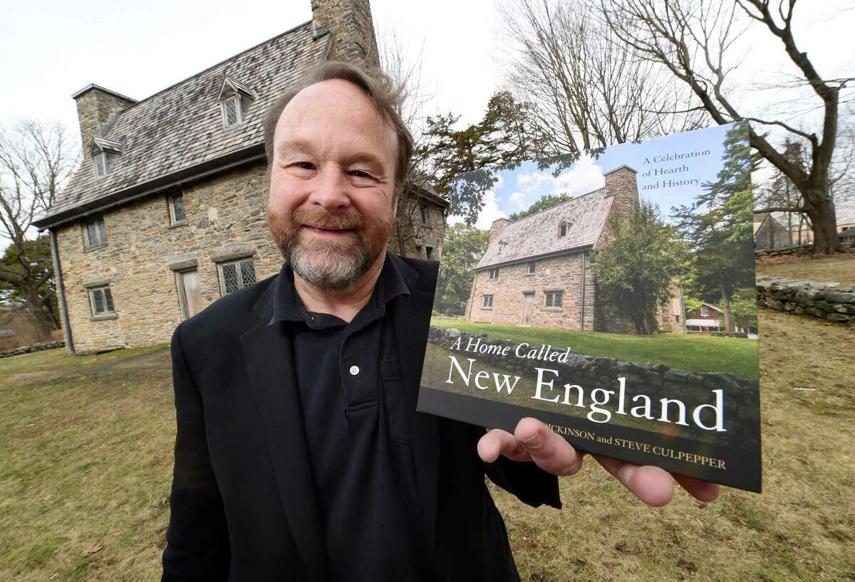 """Duo Dickinson is photographed with a book he co-authored, """"A Home Called New England,"""" in front of the Henry Whitfield House in Guilford."""
