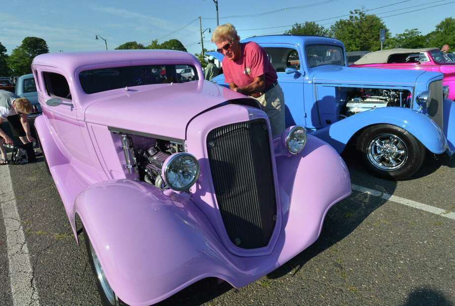 >> Click through the slideshow to see photos from Middletown's Cruise Night on Main Street from earlier this summer.  A man opens the hood of his Lilac 1934 Chevy 2 door sedan during a car cruise in Norwalk in this archive photograph. Organizers of the upcoming car cruise in East Hampton are looking for participants. Photo: File Photos / Norwalk Hour