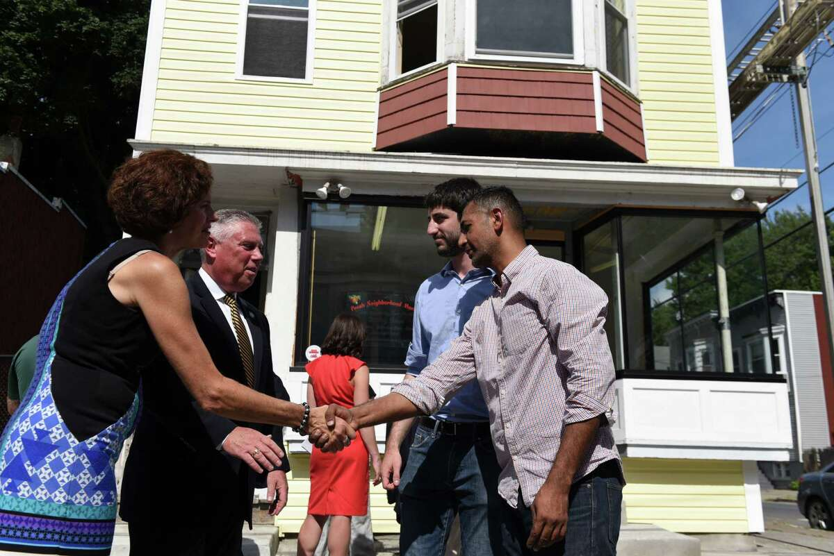 Building owner Dileep Rathore, right, shales hands with Assemblywoman Patricia Fahy, left, and Assemblyman John T. McDonald III following a press conference outside the 16 Judson Street property which Rathore is transforming into a neighborhood grocery store on Tuesday, Sept. 4 2018, in Albany, N.Y. Rathore is receiving a matching grant from the city to help renovate the facade of the building. (Will Waldron/Times Union)