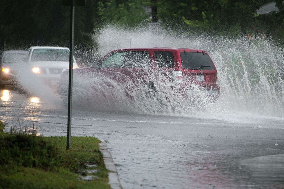 A car plows through water at the intersection of Fredricksberg and North Calaveras in San Antonio following heavy rains on Tuesday, Sept. 4, 2018. Photo: Josie Norris, San Antonio Express-News / © San Antonio Express-News