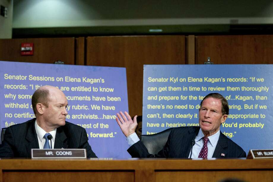 A poster with a quote from Elena Kagan's Supreme Court hearing by then Sen. Jeff Sessions is displayed behind Sen. Chris Coons, D-Del., left, and Sen. Richard Blumenthal, D-Conn., right, as President Donald Trump's Supreme Court nominee, Brett Kavanaugh, a federal appeals court judge, appears before the Senate Judiciary Committee on Capitol Hill in Washington, Tuesday, Sept. 4, 2018, to begin his confirmation to replace retired Justice Anthony Kennedy. Photo: Andrew Harnik / Associated Press / Copyright 2018 The Associated Press. All rights reserved