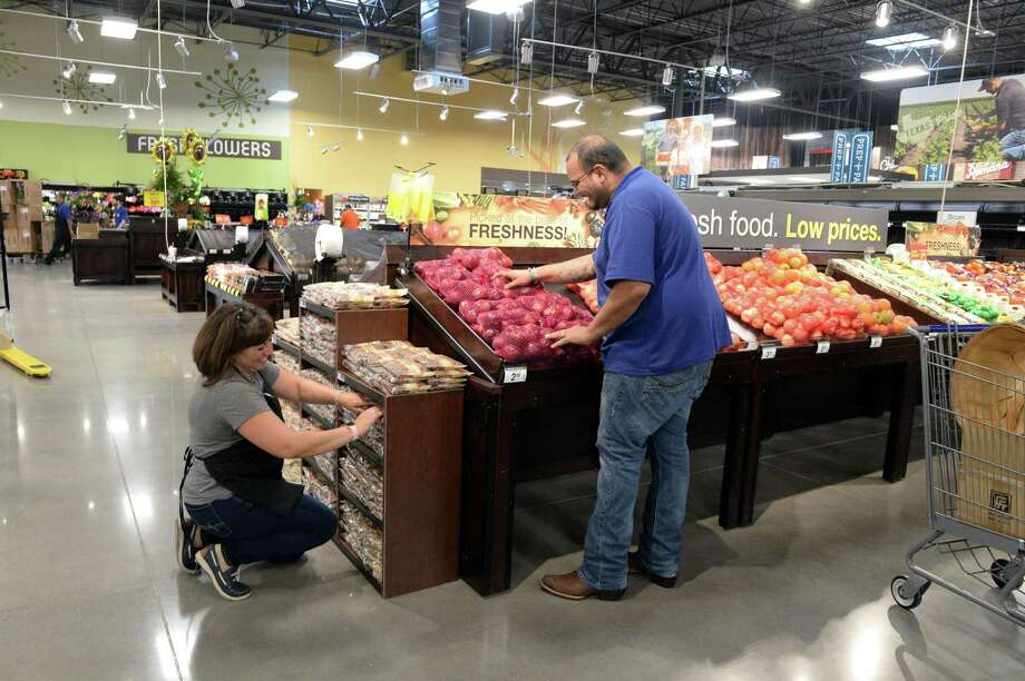 Kroger employees Sirena Borumda (left) and Paulo Garcia stock the vegetable section in preparation for the grand opening of a new 100,000-square-foot store at The Village at Riverstone in Sugar Land on Aug. 29.  Keep going to see some of Houston's international grocery stores. Photo: Craig Moseley, Houston Chronicle / Staff Photographer / ©2018 Houston Chronicle