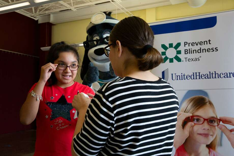Rubi Camarena is cheered on by Dr. Health E. Hound as she receives a free vision screening from a certified pediatric vision screener with Prevent Blindness Texas, as part of a back-to-school health event at the BakerRipley Leonel Castillo Community Center in Houston. UnitedHealthcare provided a $5,000 grant to Prevent Blindness Texas for the local event. Photo: Courtesy Photo By Pu Ying Huang