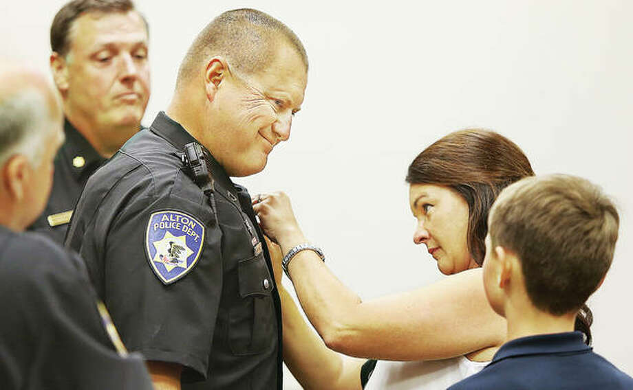 "Newly promoted Alton Police Sgt. Mark Conrad gives a fatherly look to his son, right, Tuesday as his wife, Kara, center, pins his new badge on in a promotion ceremony held at the Alton Law Enforcement Center. Alton Police Chief Jason ""Jake"" Simmons spoke briefly about the backgrounds and qualifications of the two officers promoted. Photo: John Badman 