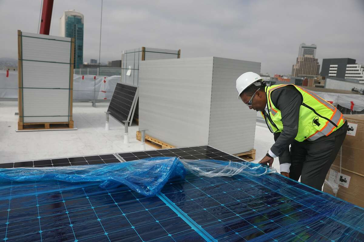 Brook Mebrahtu, senior project manager, San Francisco Department of Public Works, peels back the covering on solar panels being installed on the roof of Moscone South on Tuesday, September 4, 2018 in San Francisco, Calif.