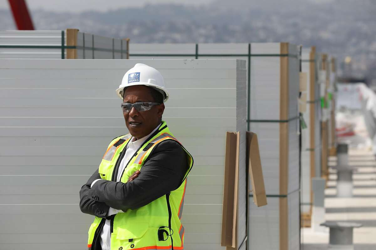 Brook Mebrahtu, senior project manager, San Francisco Department of Public Works, stands for a portrait next to stacks of solar panel on the roof of Moscone South which will be installed into an array on the roof on Tuesday, September 4, 2018 in San Francisco, Calif.