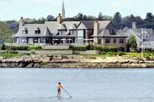 A paddleboarder navigates the water of Greenwich Cove off the Riverside section of Greenwich, Conn., Tuesday, Sept. 4, 2018. In the background is a stone mansion on Cedar Cliff Road, behind the mansion in the background the steeple of the Second Congregational Church in central Greenwich is visible. The National Weather Service is forecasting daily temperatures around 90 degrees until Thursday.