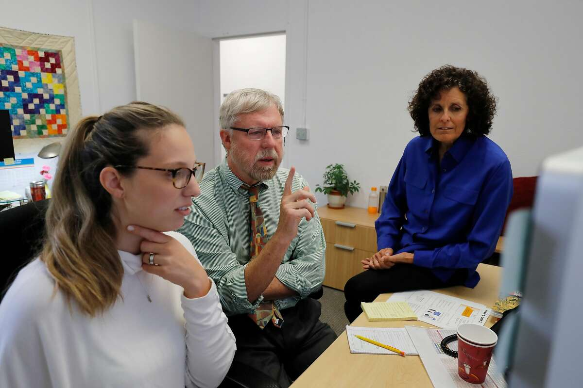 Elliott Main, MD, Medical Director of California Maternal Quality Care Collaborative, at center, meets with Communications Manager Kathryn Andrews, at left, and Administrative Director Cathie Markow as they review an online training program under development at the collaborative's office on Tuesday, Sept. 4, 2018, in Menlo Park, Calif.