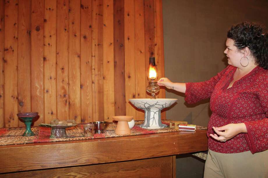 Northwoods Unitarian Universalist Church minister, The Rev. Sarah Prickett, lights her congregation's flaming chalice on the altar. The flaming chalice, Prickett explained, is one of the most prominent symbols for the religion. Photo: Jane Stueckemann / Jane Stueckemann