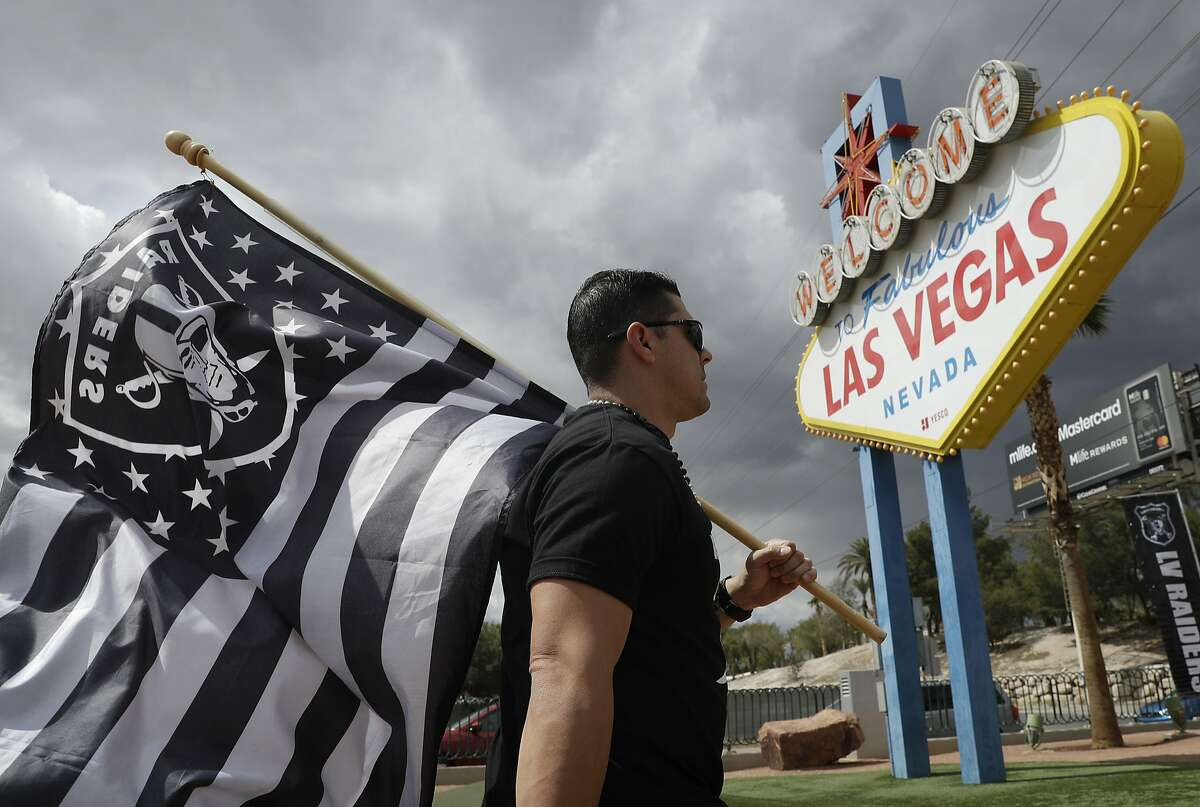 Matt Gutierrez carries a raiders flag by a sign welcoming visitors to Las Vegas, Monday, March 27, 2017, in Las Vegas. NFL team owners approved the move of the Raiders to Las Vegas in a vote at an NFL football annual meeting in Phoenix. (AP Photo/John Locher)