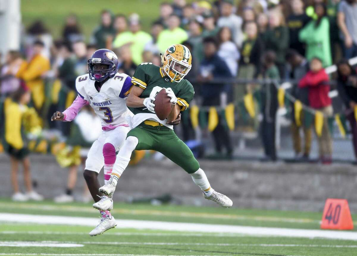 Trinity Catholic Jason Svec (6) makes a reception under pressure from Westhill Jakai Young (3) in a inner city varsity boys football game at Gaglio Field in Stamford, Connecticut on Saturday, Oct. 28, 2017. Westhill defeated Trinity Catholic 30-17.