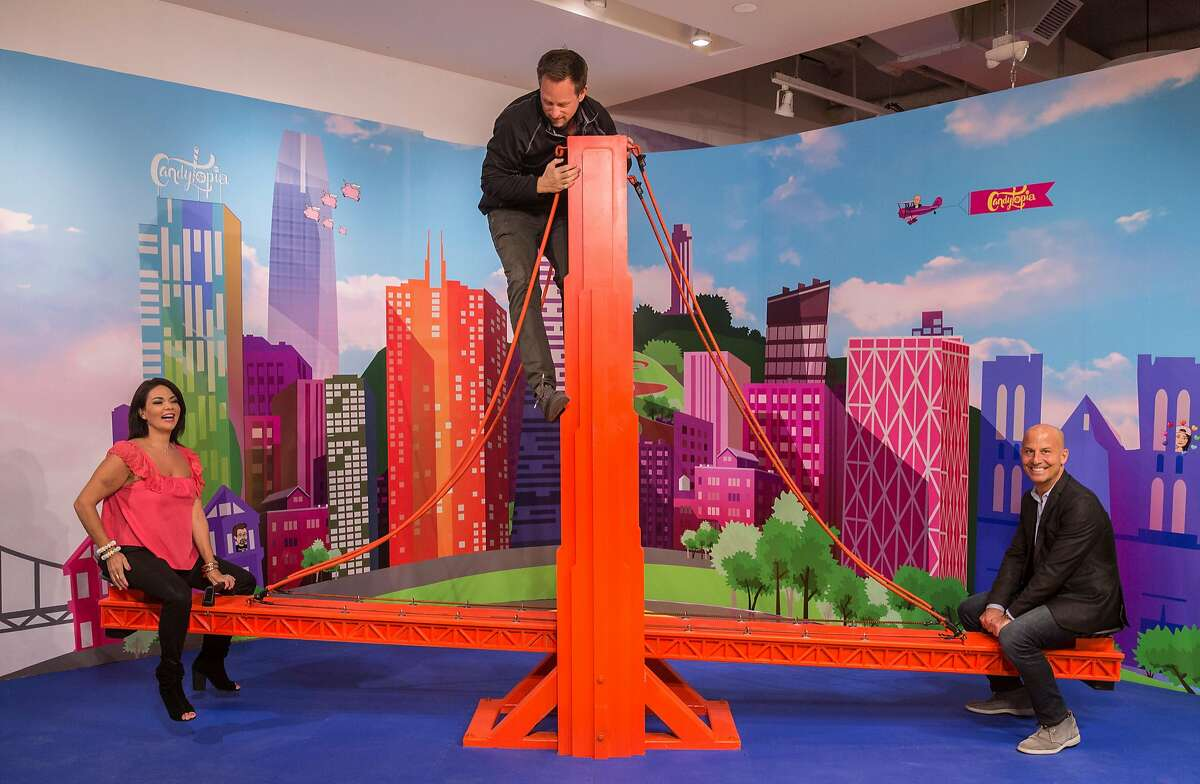 Candytopia co-founders Jackie Sorkin, left, and John Goodman, right, see-saw on a large replica of the Golden Gate Bridge while co-founder Zac Hartog climbs up the middle at Candytopia in San Francisco, Calif. Tuesday, Sept. 4, 2018.