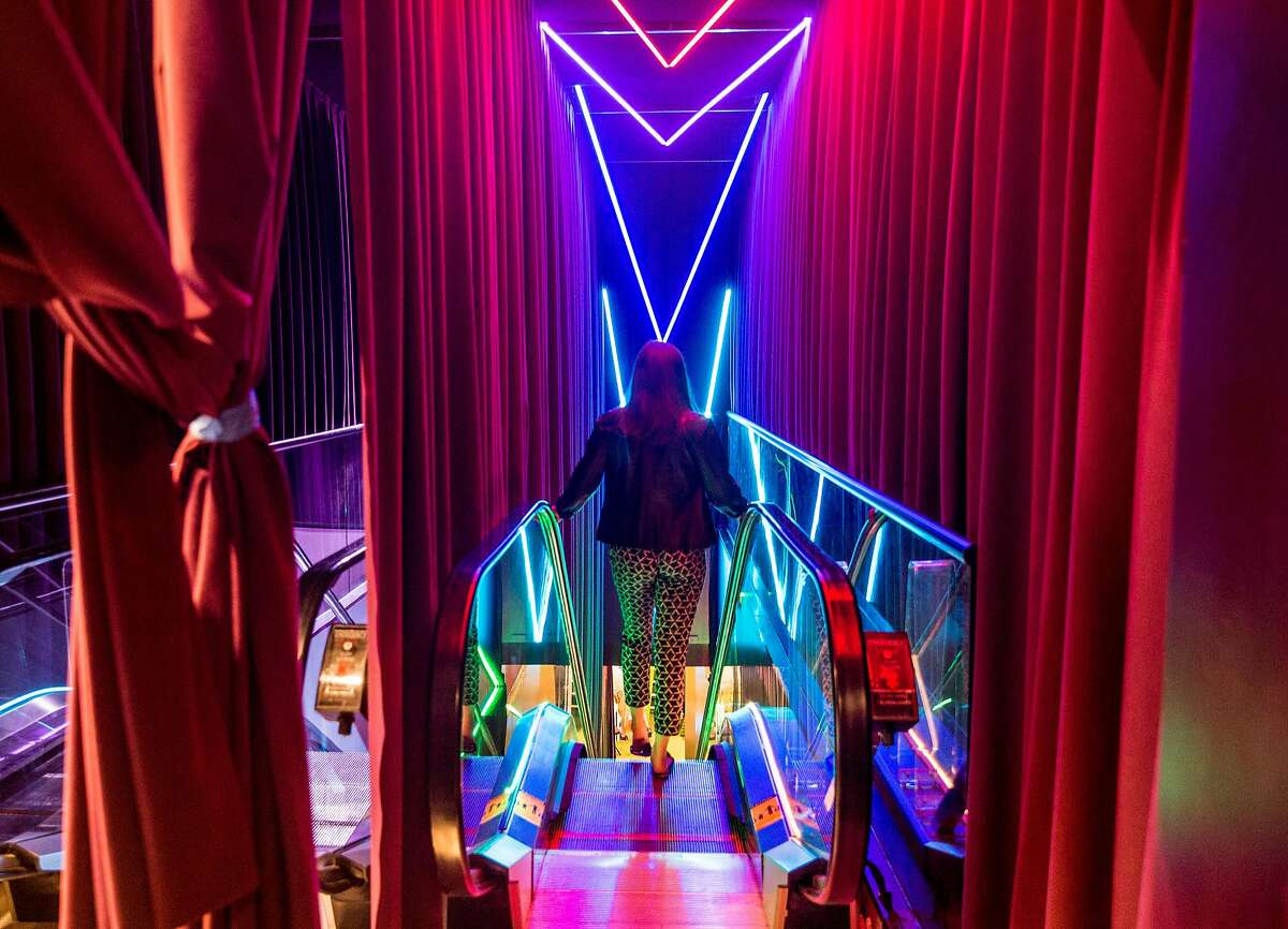 Carrie Bernstein walks down the neon-colored escalator at Candytopia in San Francisco, Calif. Tuesday, Sept. 4, 2018.