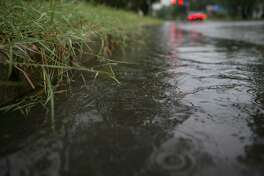 Water flows along the curb of North Calaveras in San Antonio following heavy rains on Tuesday, Sept. 4, 2018.
