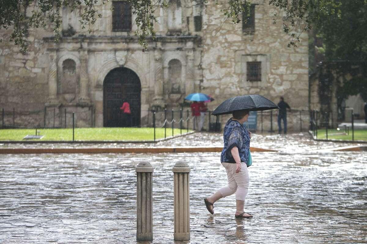 A woman walks through the rain in Alamo Plaza in San Antonio, Tuesday, Sept. 4, 2018.