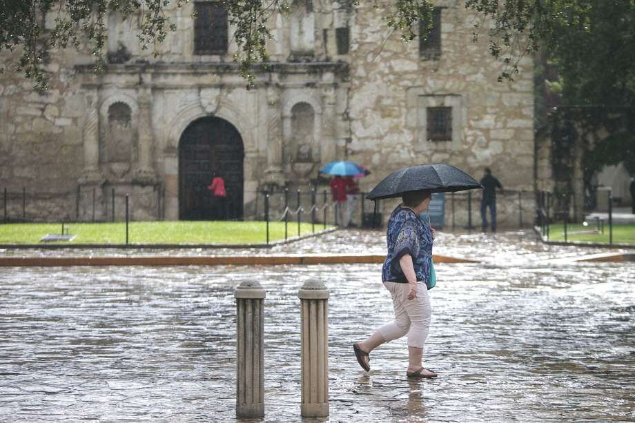 A woman walks through the rain in Alamo Plaza in San Antonio, Tuesday, Sept. 4, 2018. Photo: Josie Norris, Staff / San Antonio Express-News / © San Antonio Express-News