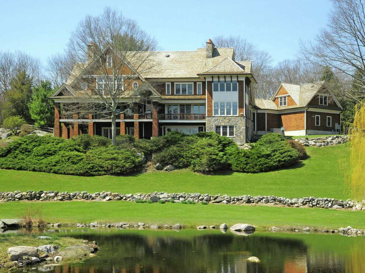 The contemporary colonial at 23 Carrington Drive in Greenwich is on 23.4 acres with two ponds and a barn with 12 stalls. The June Hill Farm property includes another house at 242 June Road in Stamford. The entire horse farm is listed for $9.950 million.