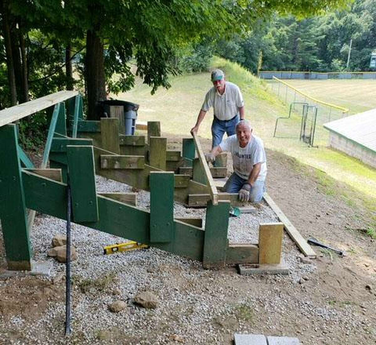 New Milford Lions Frank Cavaliero, left, and John Dunne work resconstructing two sets of wooden bleachers at one of the town's fields.