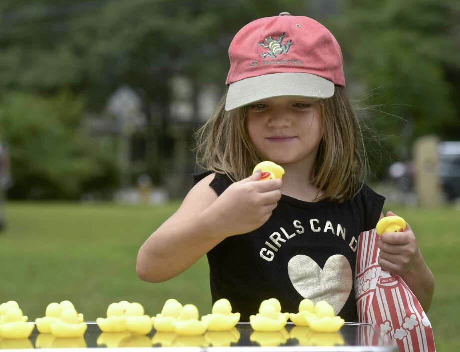 Abi Osborne, of Kent, checks the numbers on the bottom of the ducks she chose while playing the matching game at the Kent Carnival, hosted by the Kent Memorial Library on Saturday. See more photos on S3. Photo: H John Voorhees III / Hearst Connecticut Media / The News-Times
