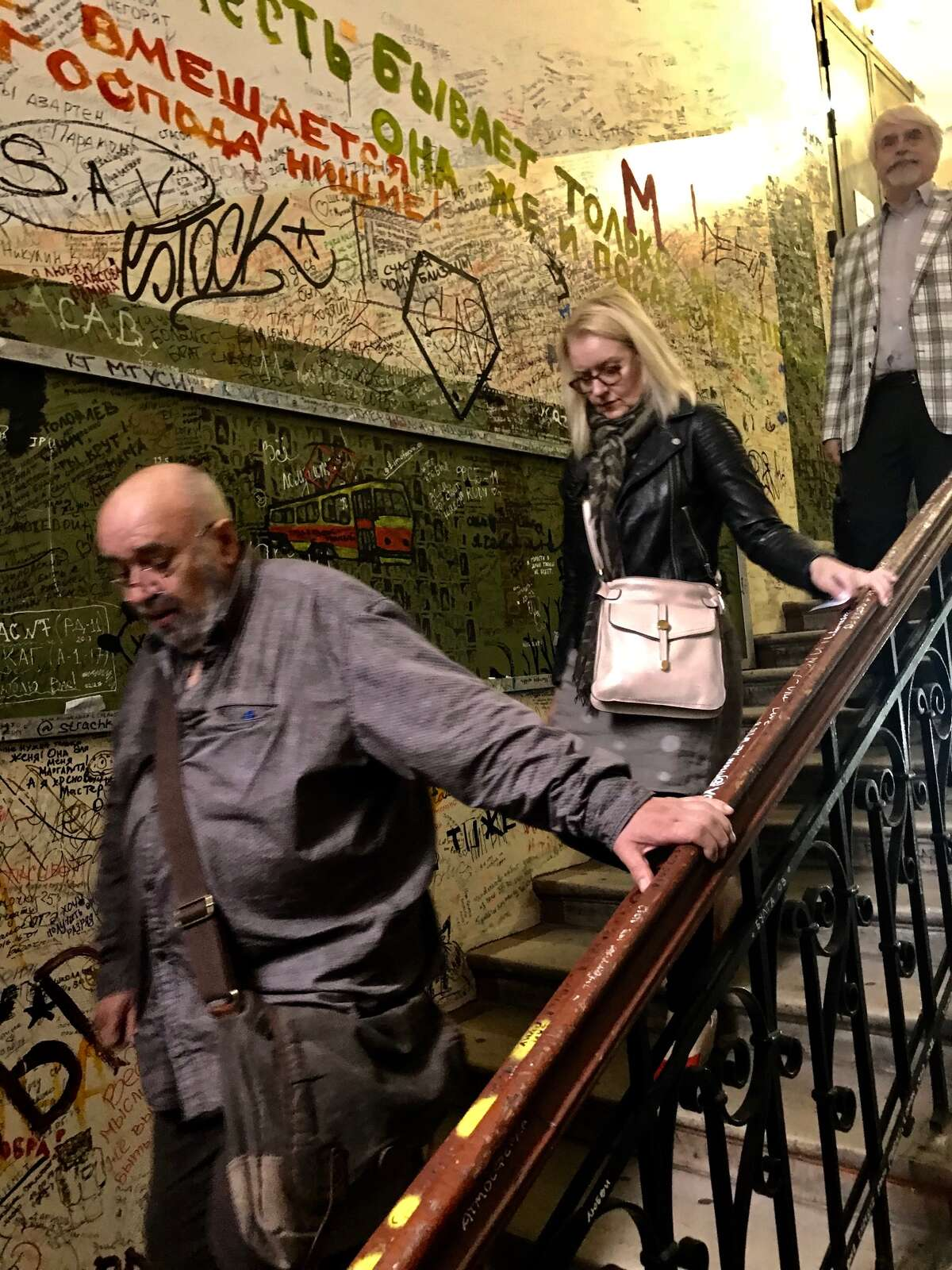 Yevgeny Popov, Mary Grondahl and Boris Evseev, pass graffiti-covered walls walking down from the fourth-floor apartment of Russian dissident writer Mikhail Bulgakov, which has become a shrine to free speech in Moscow. (Paul Grondahl / Times Union)