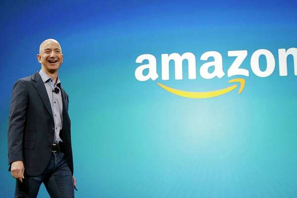 FILE - In this June 16, 2014, file photo, Amazon CEO Jeff Bezos walks onstage for the launch of the new Amazon Fire Phone, in Seattle. On Tuesday, Sept. 4, 2018, Amazon became the second publicly traded company to be worth $1 trillion, hot on the heels of Apple. The company's blowout success made its founder and CEO, Bezos, No. 1 on Forbes' billionaires list this year. (AP Photo/Ted S. Warren, File)