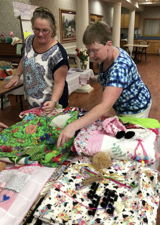 New Milford residents Shelley Killian, right, and Amy Thibodeau, left, daughters of the late Arlene Goodbou, peruse the nearly 40 sensory quilts they made and recently donated to Candlewood Valley Health & Rehabilitation Center in New Milford. Photo: Deborah Rose / Hearst Connecticut Media / The News-Times  / Spectrum